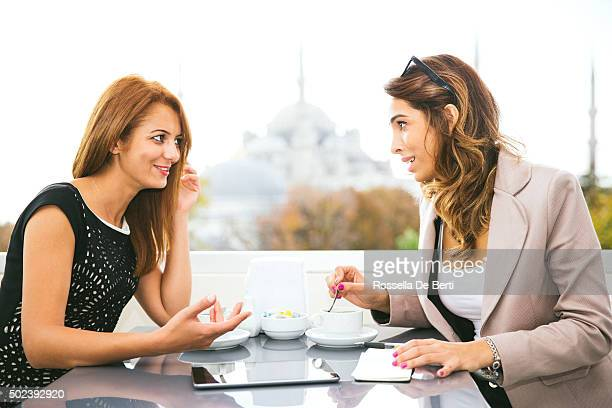 Joyeux femmes d'affaires travaillant au café