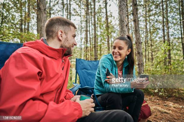 cheerful camping couple enjoying talking and tea in the forest - images stock pictures, royalty-free photos & images