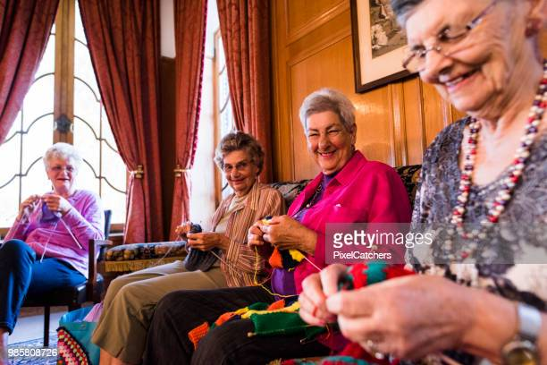 cheerful candid portrait of senior women knitting - organised group stock pictures, royalty-free photos & images