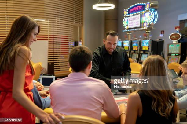 cheerful card dealer at the casino offering more cards at the blackjack table - hispanolistic stock photos and pictures
