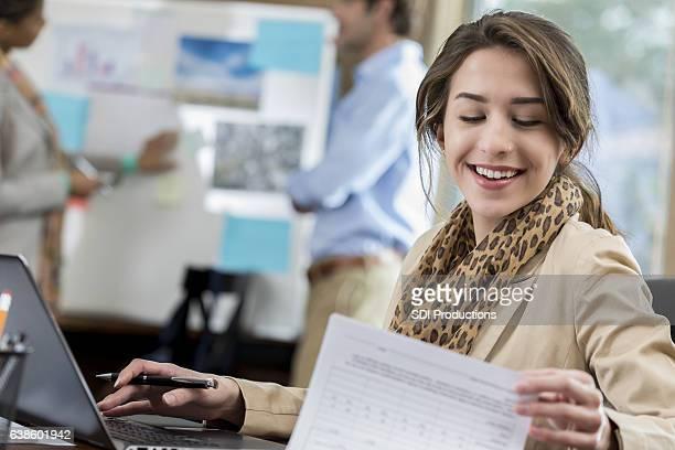 Cheerful Caucasian businesswoman examines document