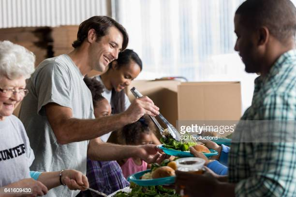 Cheerful Caucasian man serves healthy meal in soup kitchen