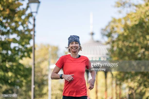 cheerful caucasian sportswoman in early 50s running at park - clapham common stock pictures, royalty-free photos & images