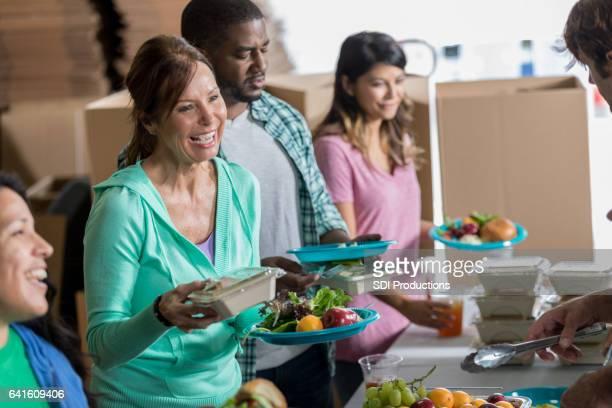 Vrolijke Kaukasische vrouw ontvangt maaltijd in gaarkeuken