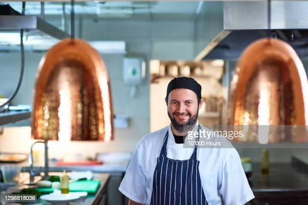 cheerful chef smiling towards camera in restaurant kitchen - employee stock pictures, royalty-free photos & images