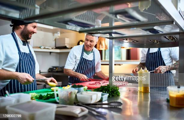 cheerful chefs preparing food in commercial kitchen - mature adult stock pictures, royalty-free photos & images