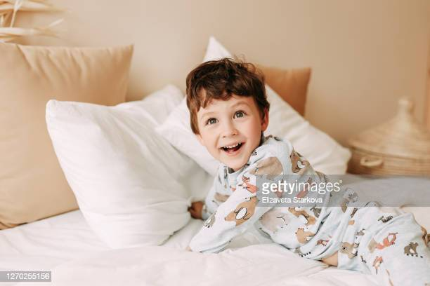 cheerful child in pajamas laughs and has fun on the bed in a cozy home - pyjamas stock pictures, royalty-free photos & images