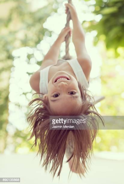 cheerful child swinging on rope - schommelen bungelen stockfoto's en -beelden
