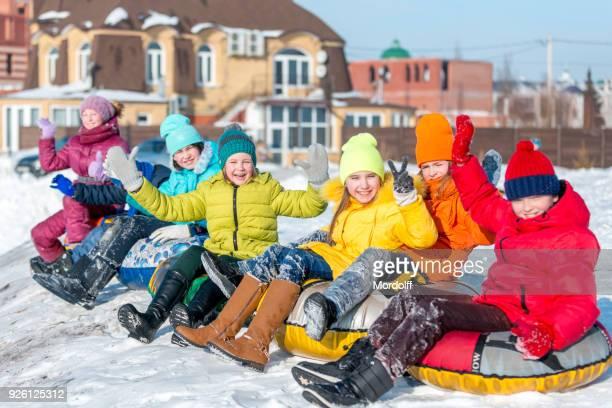 元気な子どもは膨脹可能なそりにダウン雪の丘を転がり