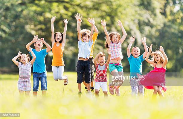 Cheerful children jumping in nature.