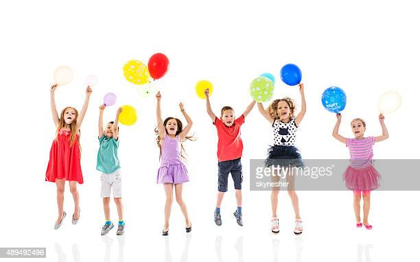 Cheerful children jumping with balloons in their hands.