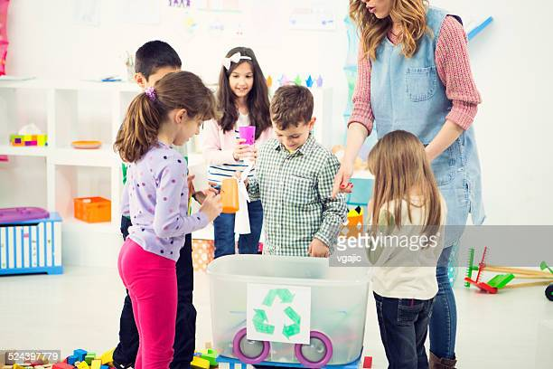 Cheerful Children Learning About Recycling in a kindergarden.
