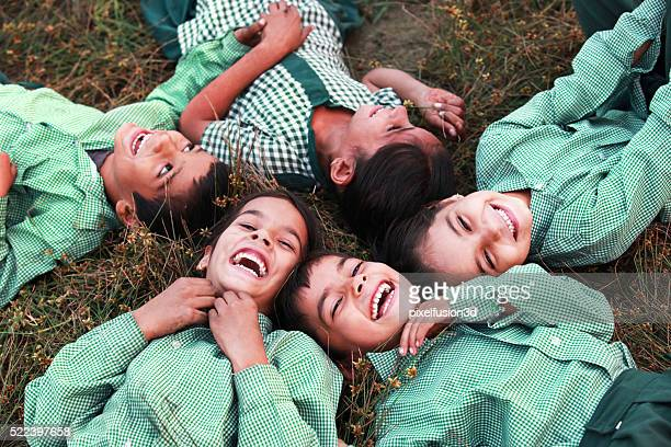 cheerful children lying dawn on grass