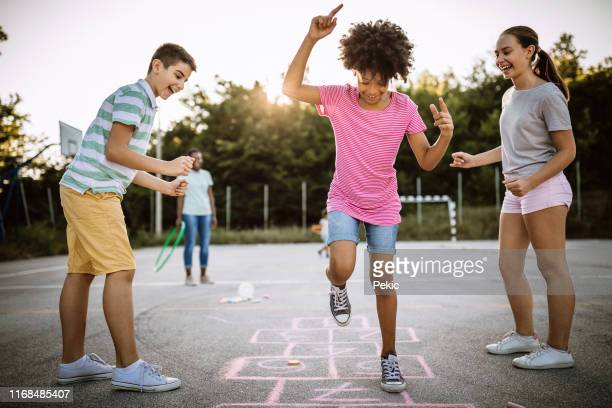 cheerful children playing hopscotch on school yard - hopscotch stock pictures, royalty-free photos & images