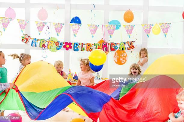 Joyeux enfants jouant avec parachute sur fête d'anniversaire.