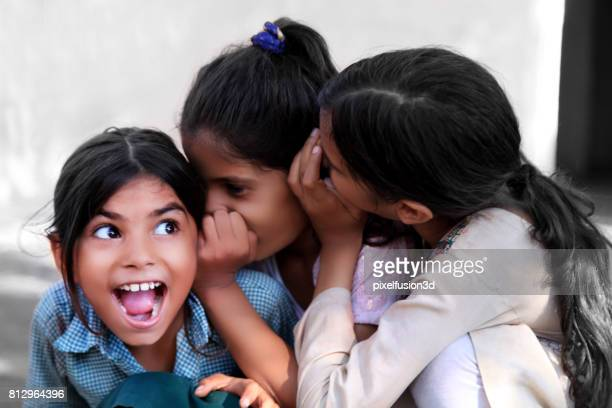 cheerful children whispering in ear - indian culture stock pictures, royalty-free photos & images