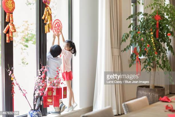 Cheerful children with Chinese New Year paper-cut for window decoration