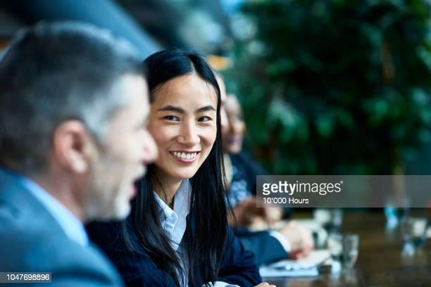 cheerful chinese businesswoman smiling towards colleague in meeting - trabalhadora de colarinho branco imagens e fotografias de stock