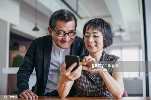 cheerful chinese couple using smartphone - asia stock pictures, royalty-free photos & images