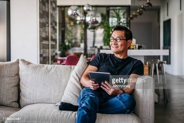 cheerful chinese man with tablet looking away and smiling - using digital tablet stock pictures, royalty-free photos & images