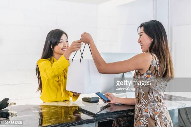 cheerful chinese sales assistant handing bag to customer - yellow dress stock pictures, royalty-free photos & images