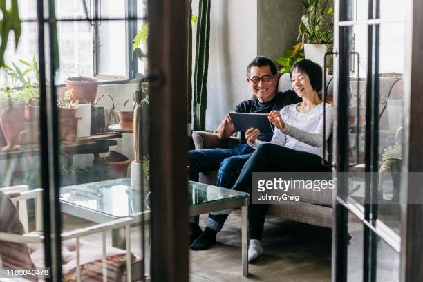 cheerful chinese woman showing man digital tablet in conservatory - pension stock pictures, royalty-free photos & images