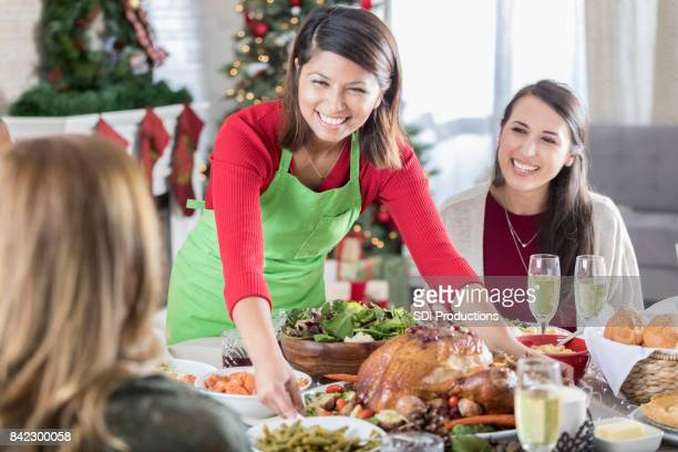 Cheerful Christmas dinner hostess places whole turkey on table
