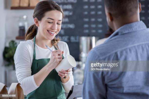 cheerful coffee shop barista writes order on cup - disposable cup stock pictures, royalty-free photos & images