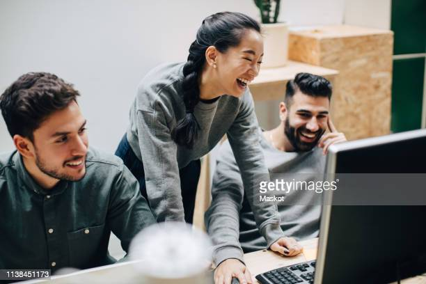 cheerful colleagues discussing while looking at computer on desk in office - surfing the net stock pictures, royalty-free photos & images