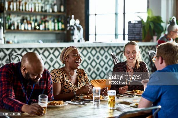 cheerful colleagues enjoying relaxed business lunch - friendship stock pictures, royalty-free photos & images