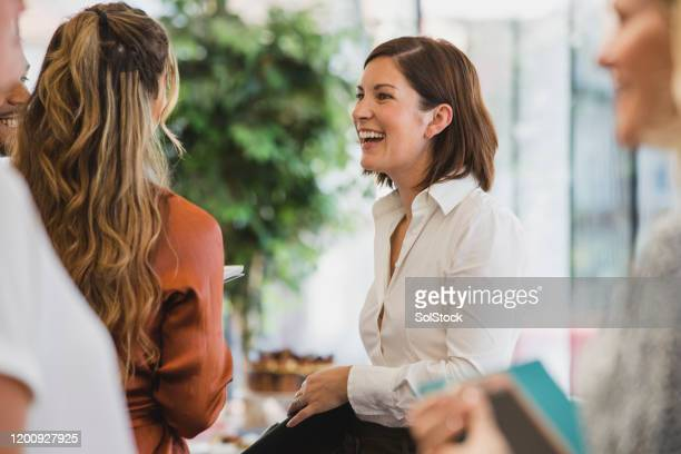 cheerful colleagues laughing during corporate event - greeting stock pictures, royalty-free photos & images