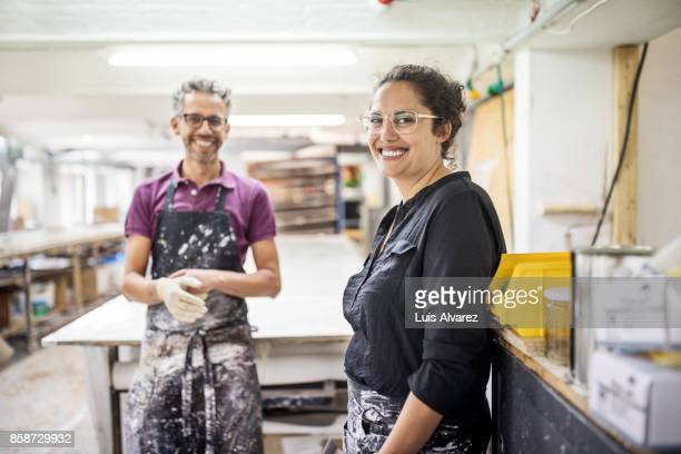 cheerful colleagues standing at workshop - vanguardians stock pictures, royalty-free photos & images