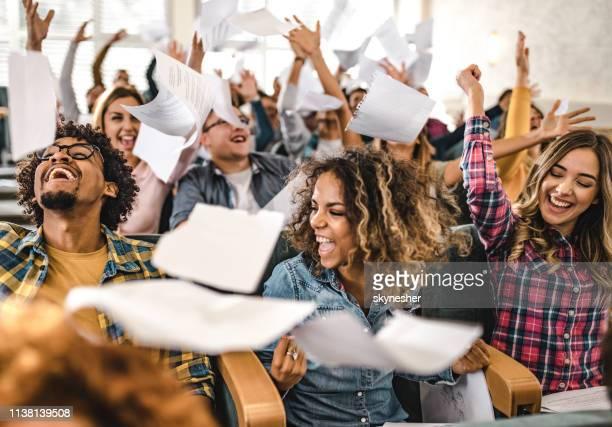 estudiantes universitarios alegres celebrando el fin del año escolar en la sala de conferencias. - acabar fotografías e imágenes de stock