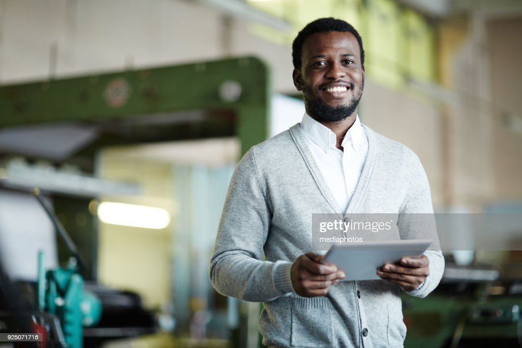 Cheerful confident African printing worker with tablet : Stock Photo