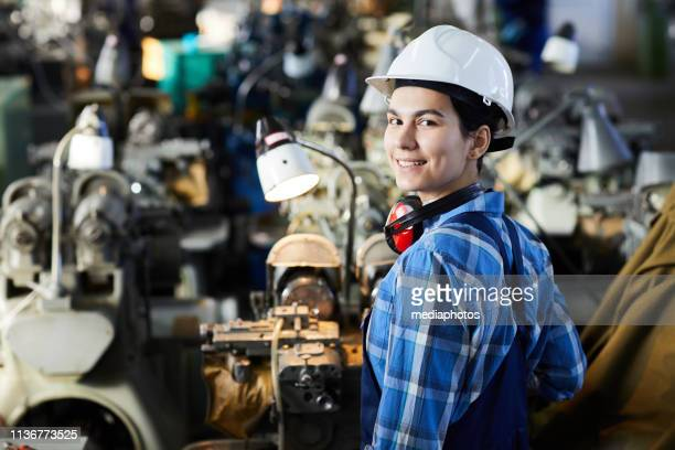 Cheerful confident attractive woman in construction hardhat standing at lathe machine and turning back while looking at camera, woman in industry concept