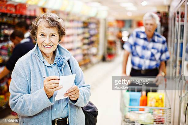Cheerful, confident senior woman shopper checks shopping list in supermarket