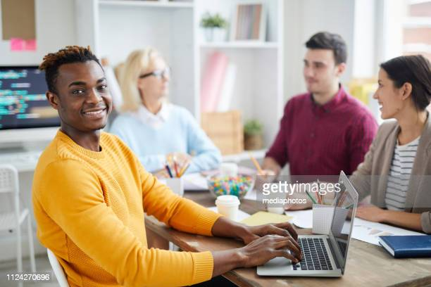 Cheerful confident young black man in yellow sweater sitting at table and looking at camera while making notes into laptop during meeting