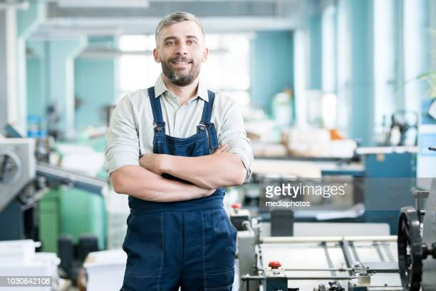 cheerful content confident bearded typography worker in overall crossing arms on chest and looking at camera while standing among printing machines - mechanical engineering stock pictures, royalty-free photos & images