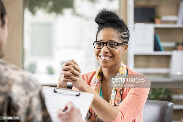 cheerful counselor meets with male army veteran - form filling stock photos and pictures