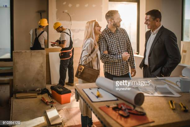 Cheerful couple and building contractor talking at construction site.
