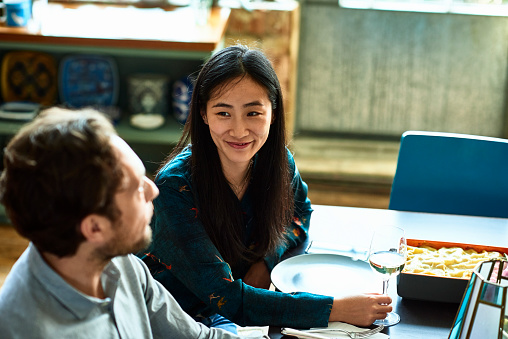 Cheerful couple at dinner table talking and smiling - gettyimageskorea