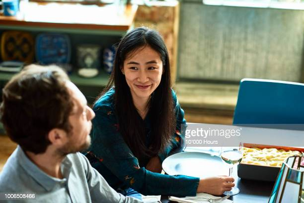 cheerful couple at dinner table talking and smiling - 35 year old man stock pictures, royalty-free photos & images