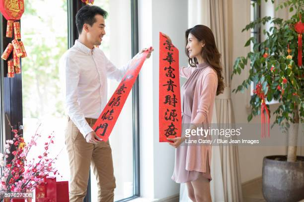 Cheerful couple celebrating Chinese New Year with couplets