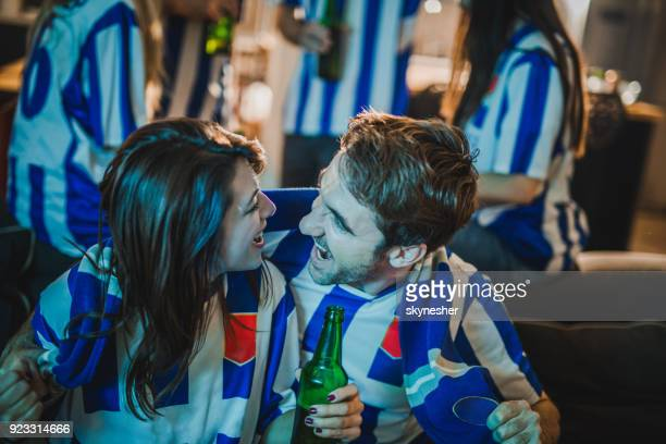 Cheerful couple celebrating the victory of their soccer team at home.