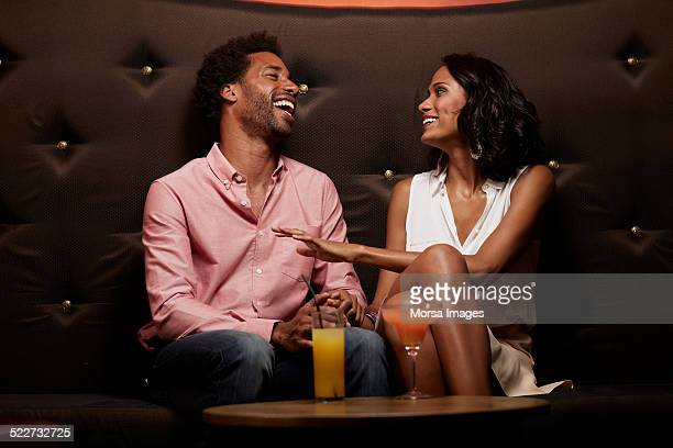 Cheerful couple conversing on sofa at nightclub