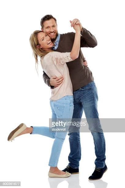 Cheerful couple dancing over white