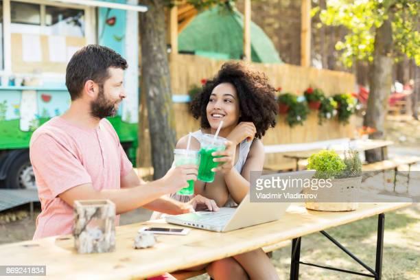 Couple gai boire des cocktails et à l'aide d'ordinateur portable