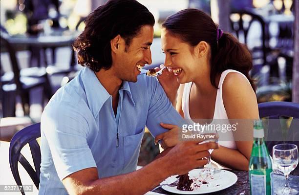 Cheerful couple eating cake