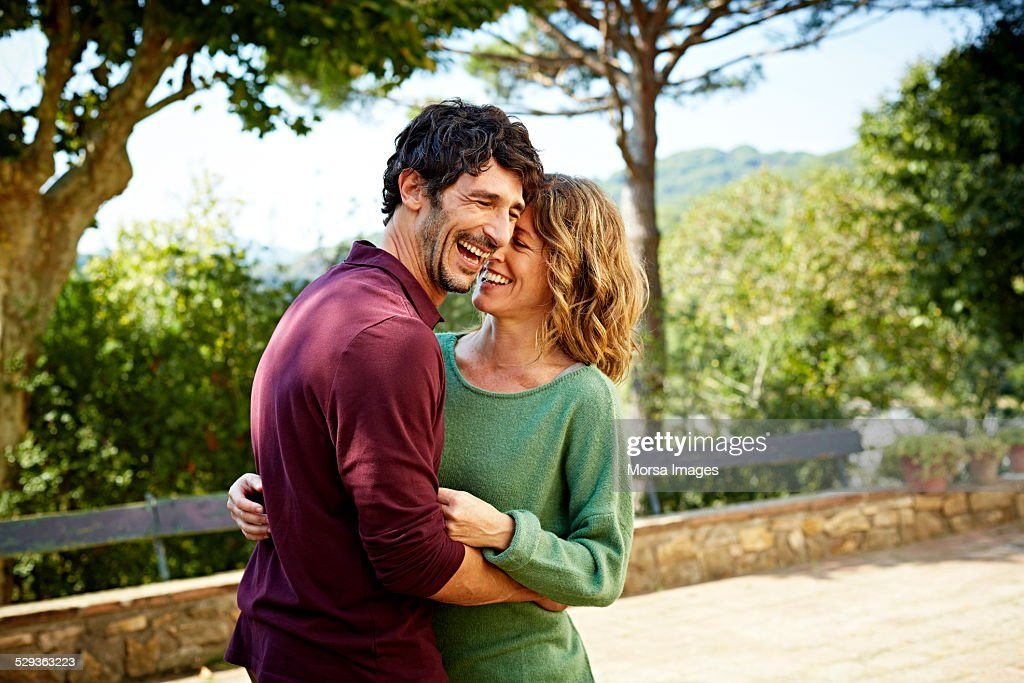 Cheerful couple embracing in park : Stock Photo