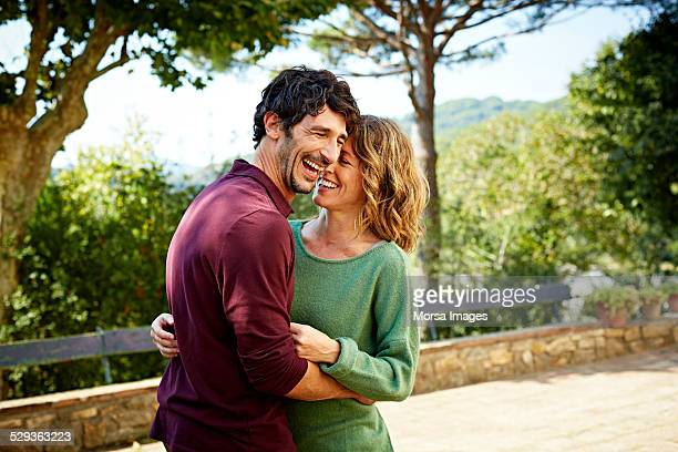 cheerful couple embracing in park - enthousiaste photos et images de collection